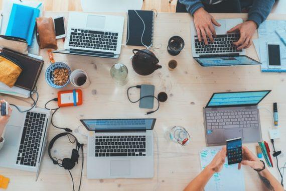 bird's eye view of 5 team memvers working on their computers