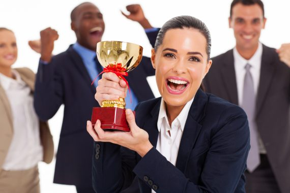 employees holding a trophy and cheering
