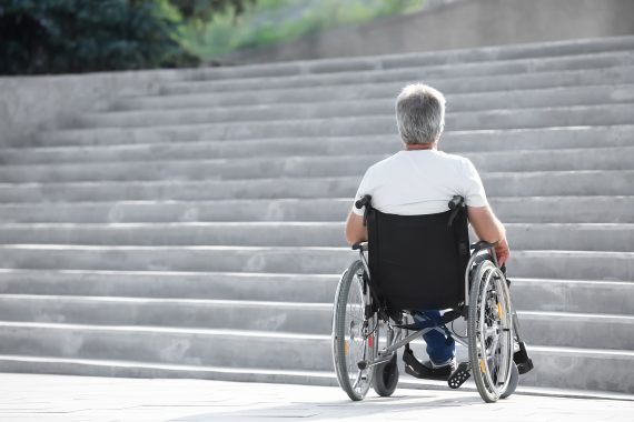 Senior man in wheelchair stopped by stairs